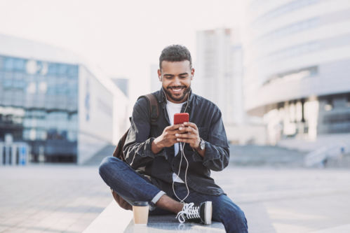 Jeune homme souriant qui regarde son téléphone