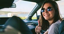Jeune femme au volant souriante